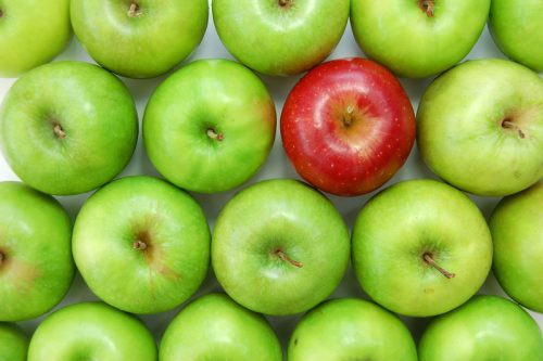 green apples with one red apple