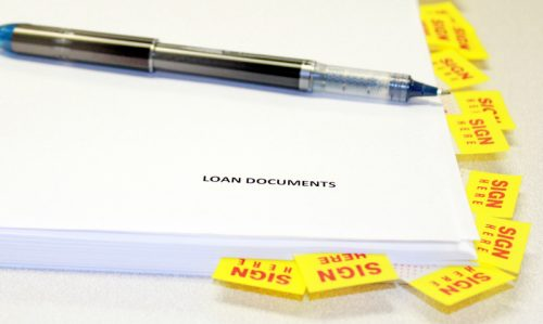 Loan documents with sign here stickers