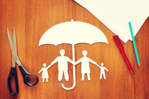 Paper doll family under paper umbrella